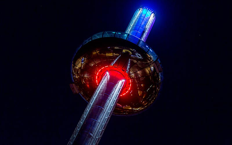 A close up of British Airways i360 illuminated in red and blue at night time