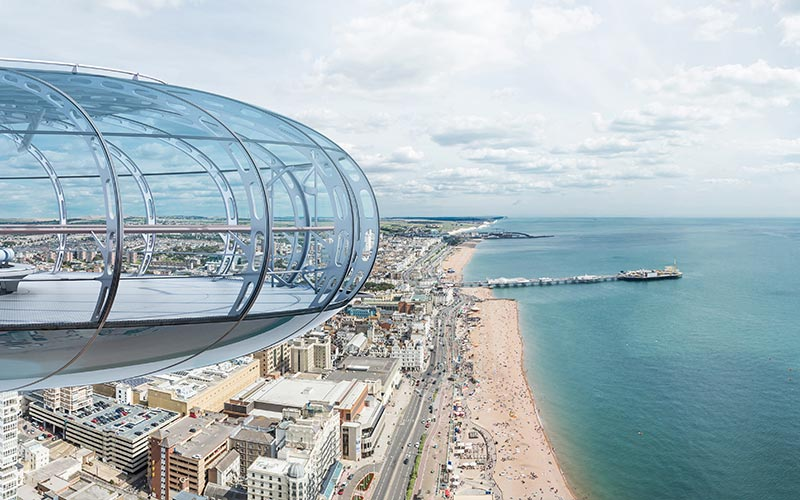 The outside of the British Airways i360 pod, looking over the beach and Brighton skyline