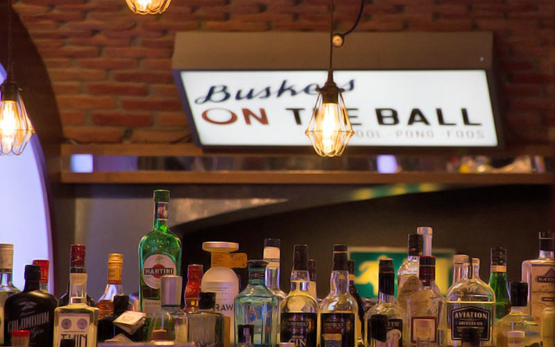 Buskers on the Ball sign on the wall, above a bar, with a lamp hanging in the foreground