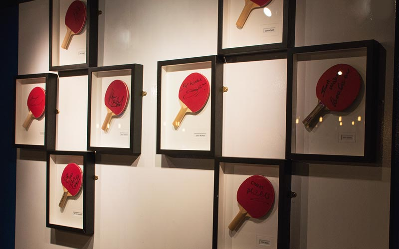 Framed ping pong bats, hung on a wall