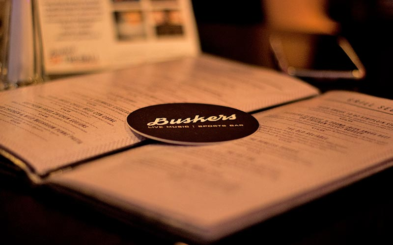 A Buskers Bar coaster, placed on top of an open menu