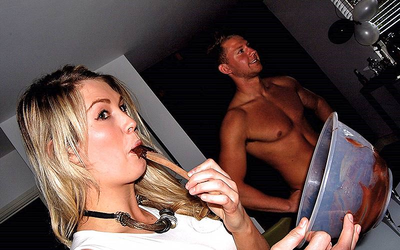 Blonde woman licks chocolate off wooden spoon with topless man in background