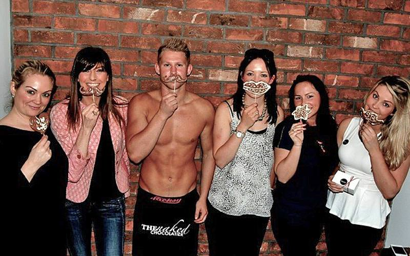 A group of women show off chocolate creations alongside a topless chocolatier