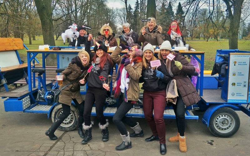 A group of women standing next to a beer bike