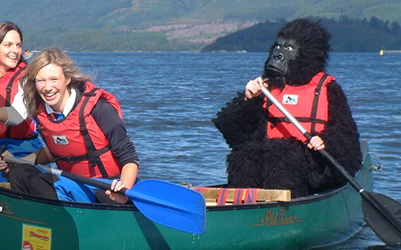 A hen dressed as in a gorilla costume kayaking on Loch Lomond