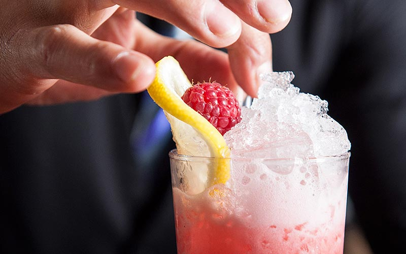 A man placing fruit on top of a cocktail