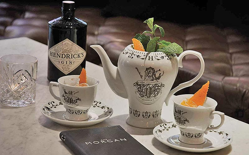 A teapot with two cups and a bottle of Hendrick's gin on the table