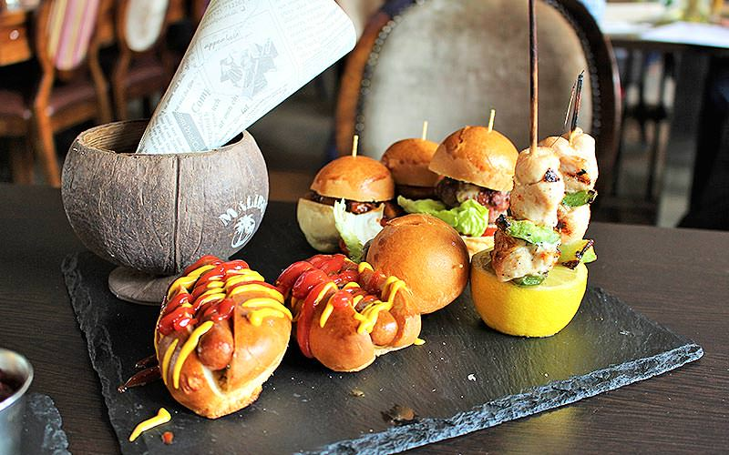 Mini burgers, chicken skewer balanced on a lemon and two mini hotdogs on a black slate