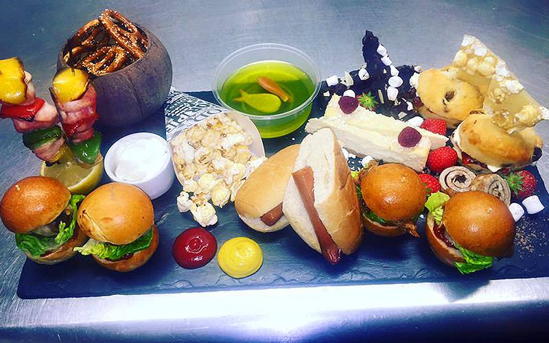 Freaky afternoon tea, featuring mini burgers, hotdogs, cakes, pretzels in a wooden-style bowl and chiecken skewers on top of a lemon
