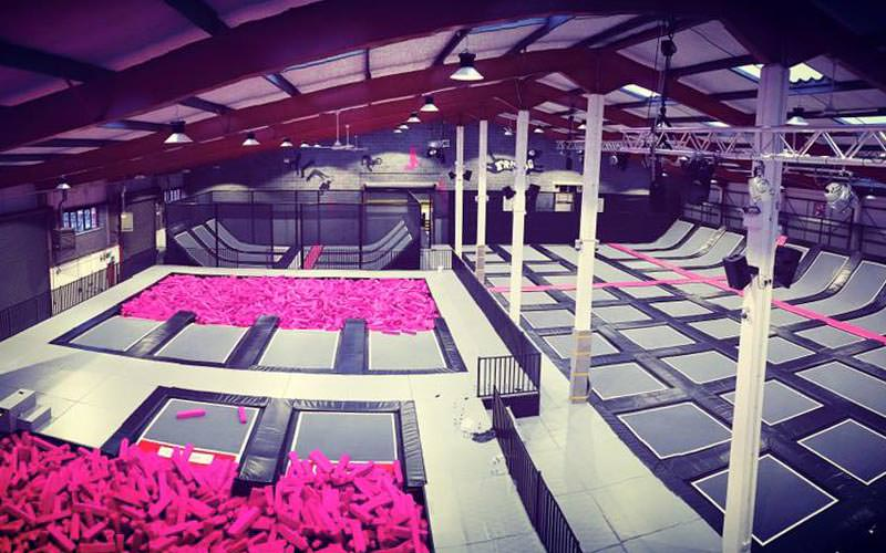 Two pools of pink foam blocks, with trampolines in the floor on the other side