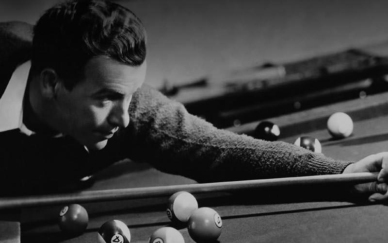 Black and white image of Paul Newman playing pool