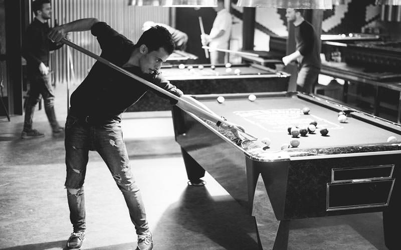 Black and white image of people playing pool