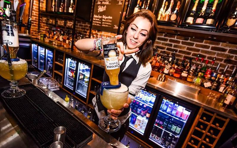 A female bartender holding a cocktail with a Corona sticking out the top