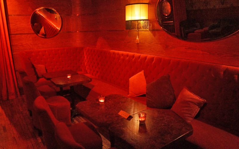 An intimate red booth in Odeon Bar