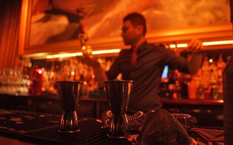 A bartender making cocktails behind a bar