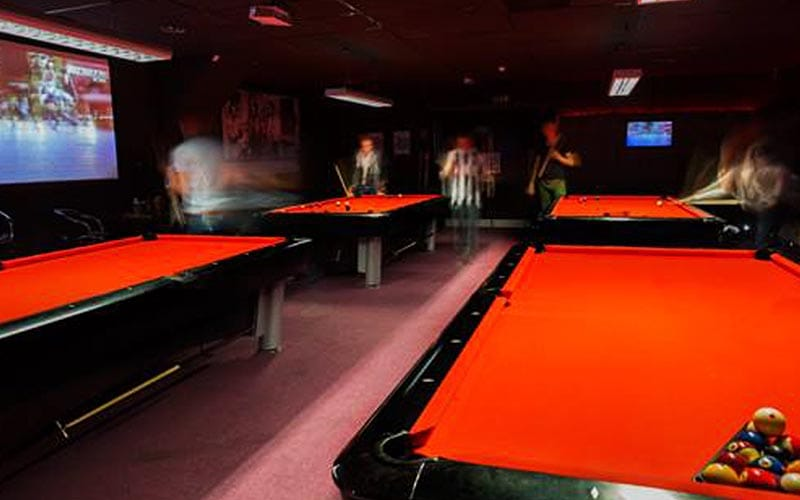 4 red pool tables, with people playing on the back two tables.