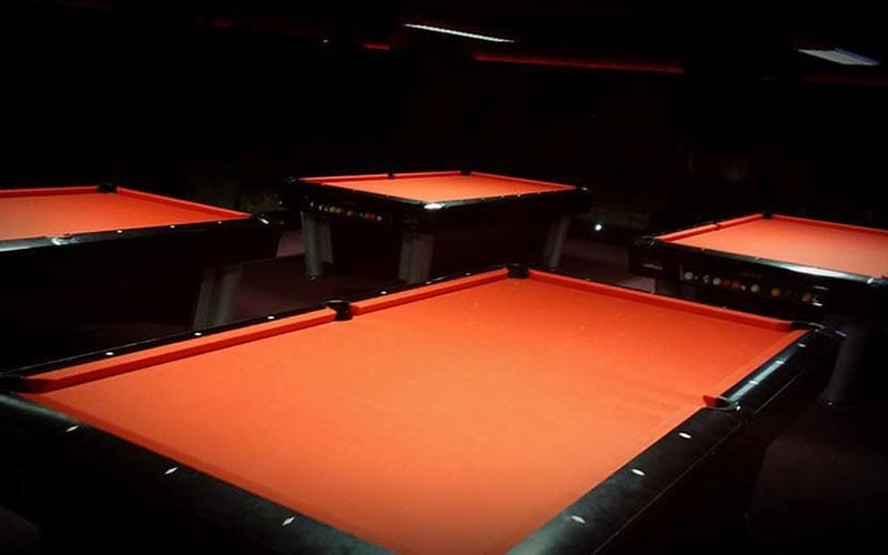Four red surfaced pool tables with light shining on them.