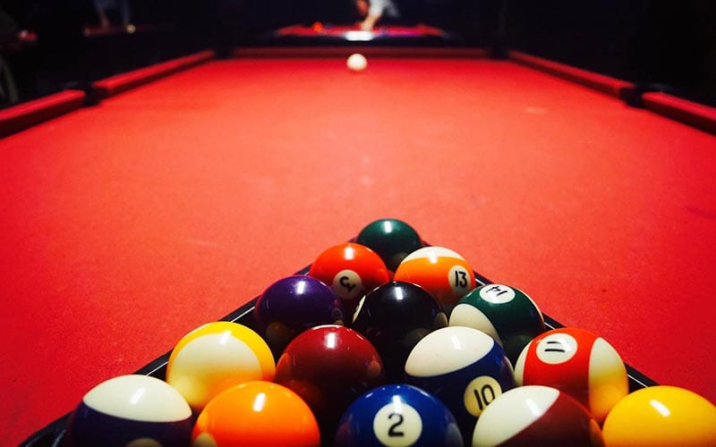 Rack of pool balls, in a triangle, sat on a red table with the white cue ball at the opposite end of the table.