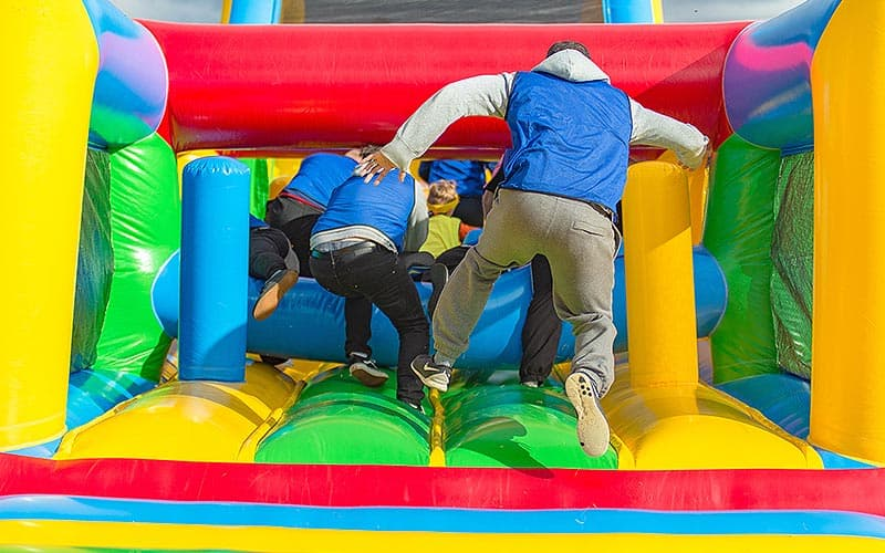 Some people running onto a bouncy castle