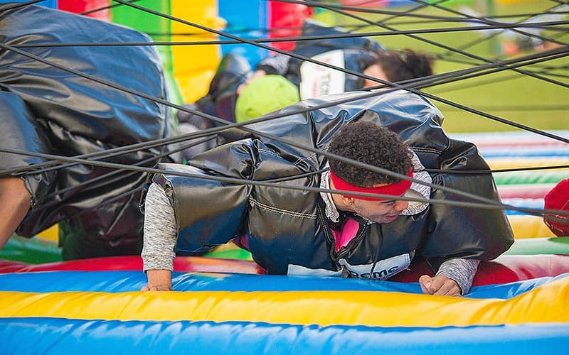 Some people in sumo suits getting through the spider's web challenge