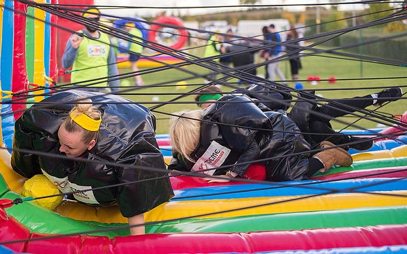 Some people in sumo suits attempting to climb through the spider's web style inflated obstacle course