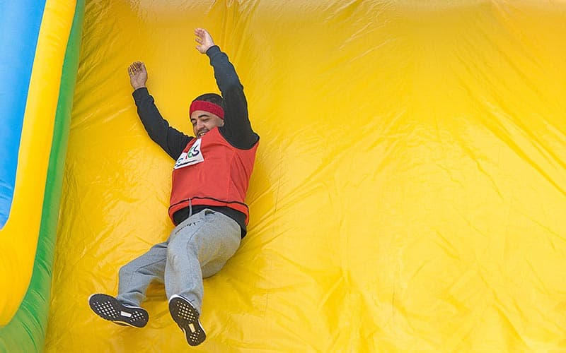 A man sliding down a giant, inflated slide