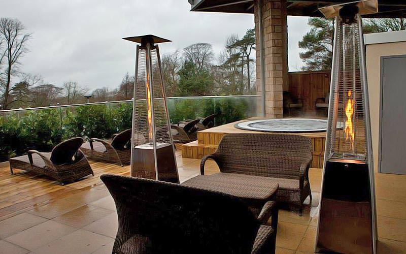 An outdoor Jacuzzi area with firepits and seats on the decking