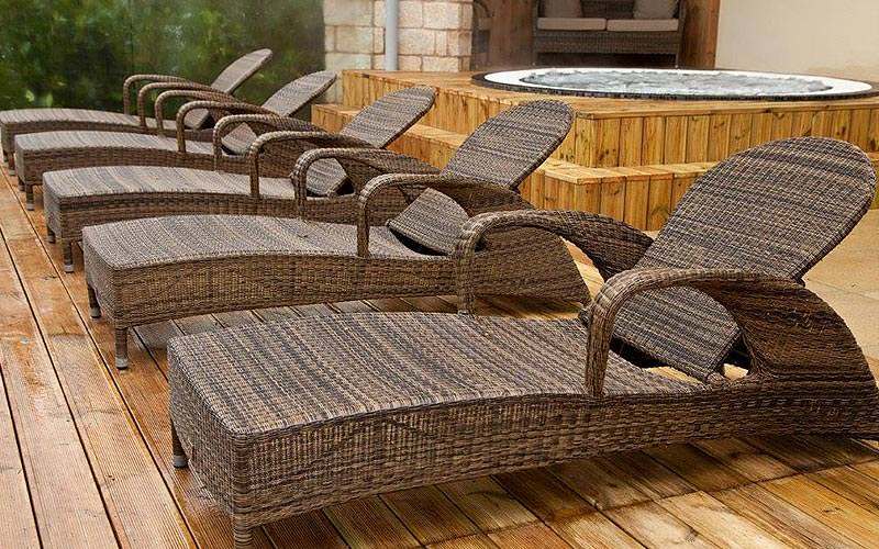 Some wicker chairs on the decking with a Jacuzzi in the background