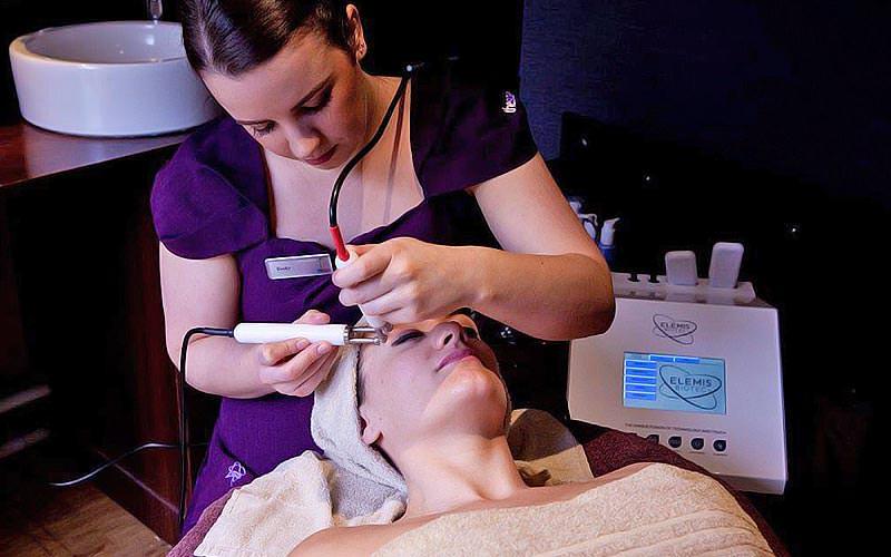 A woman receiving a facial treatment in a spa