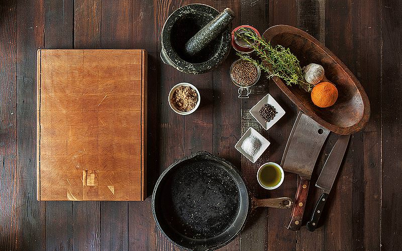 Knives, pots and ingredients on a wooden table