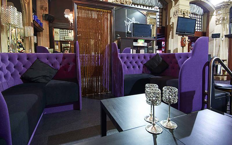 Image of a room with purple corner sofas with black wooden tables with wine shaped candle holders and flat screen tvs placed around the walls