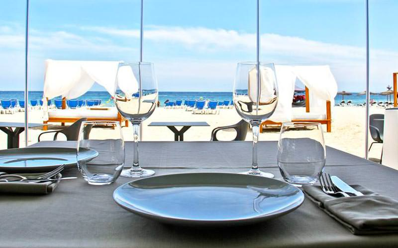 A table set for dinner with the beach and sunbeds in the background
