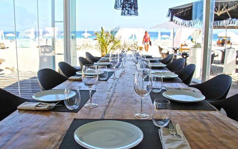 A long table set for dinner with the beach in the background