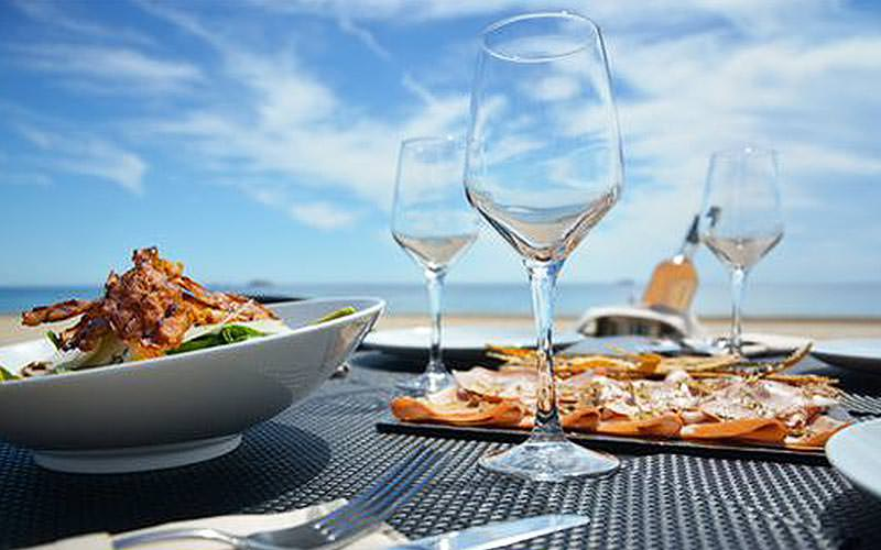 Several dishes of food on a table on the beach