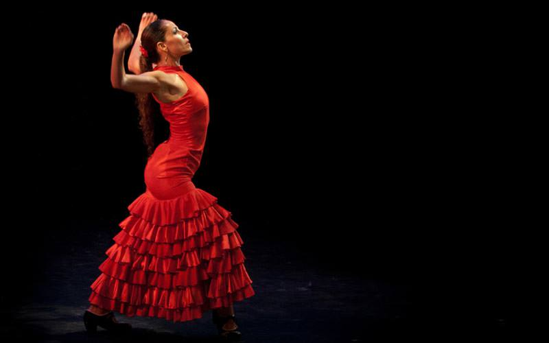 Image of a woman wearing a long red ruffled dress standing with her arms in the air at her sides