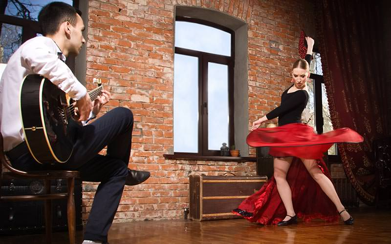 Image of a man sitting playing a guitar and a woman dressed with a floaty red skirt and black top dancing