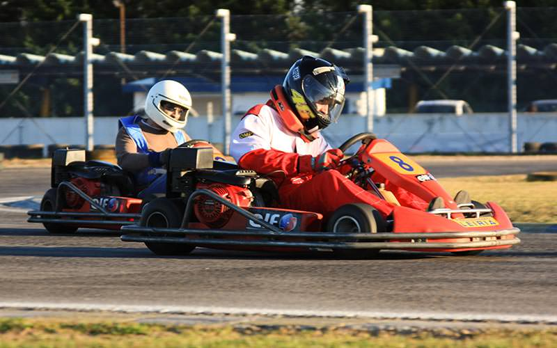 Image of two people wearing helmets and overalls driving go karts on an outdoor track
