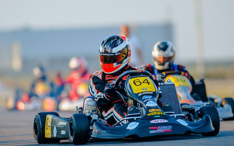 Image of a group of people wearing helmets and overalls racing go karts on an outdoor track