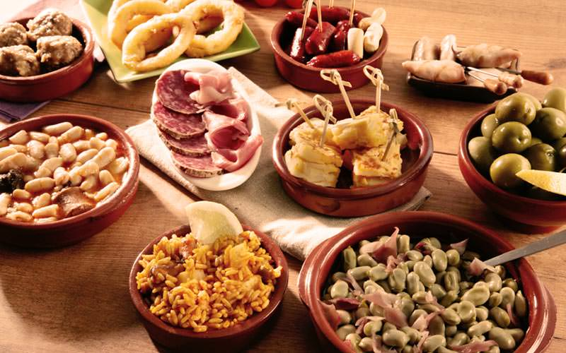 Image of a selection of tapas dishes on a wooden table