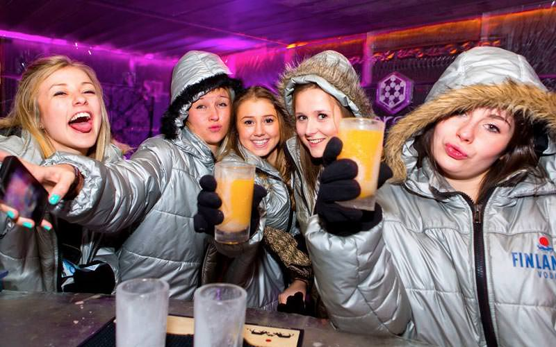 Image of a group of women at the bar wearing fur silver parkers holding drinks inside the ice bar