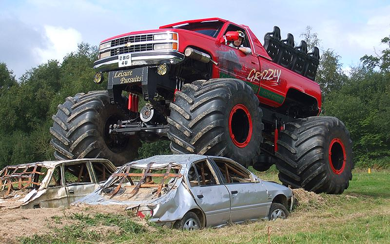 Red monster truck driving over a car in a field