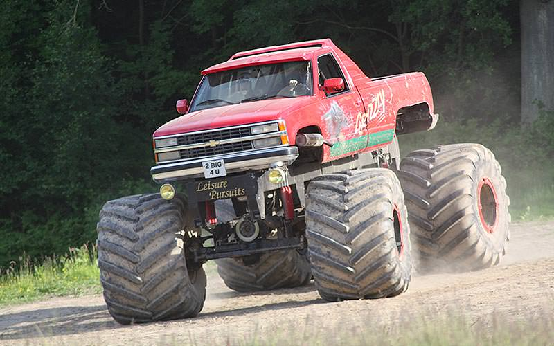 People driving a red monster truck down a dirt path