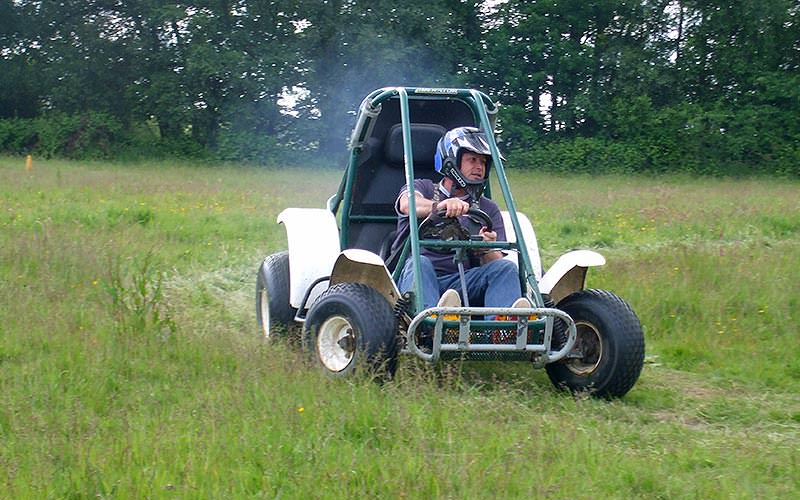 A man in a rally kart in the field