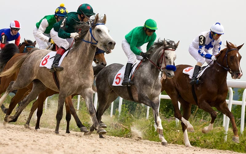 Some horses racing across a race track