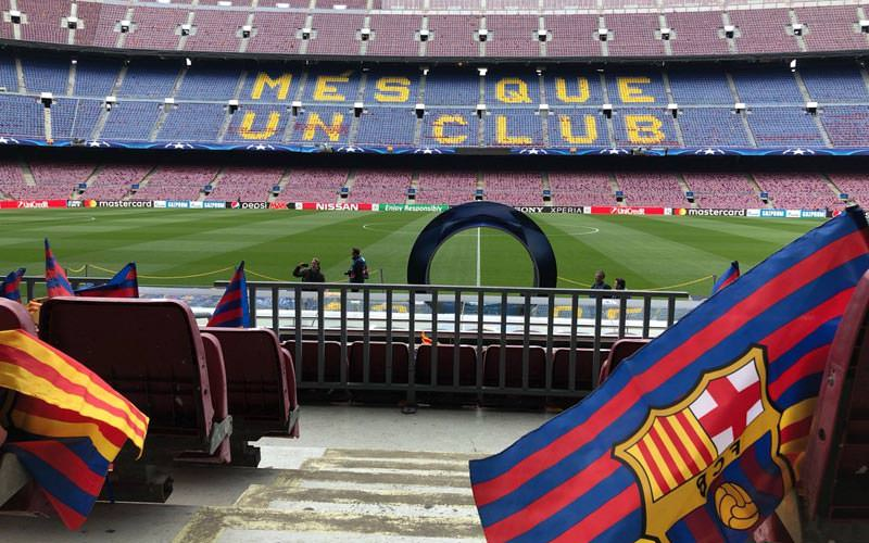 Image of the stadium from the bottom turnstile with barcelona flags looking out onto the pitch