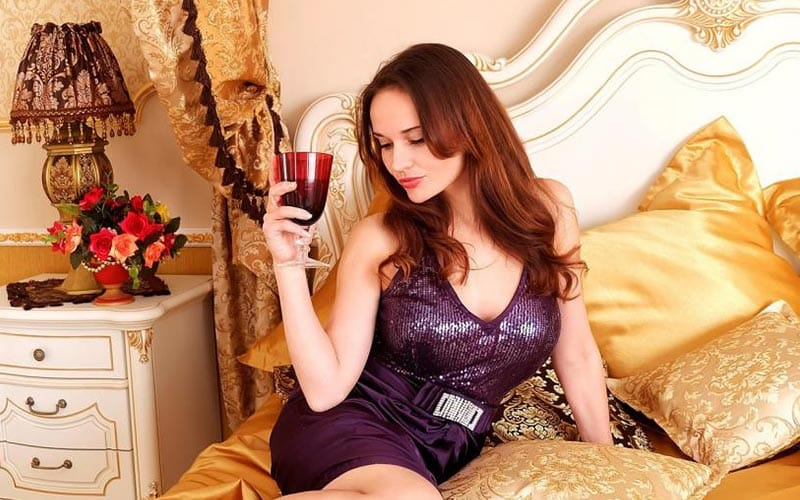 A girl sitting on a bed, holding a glass of wine