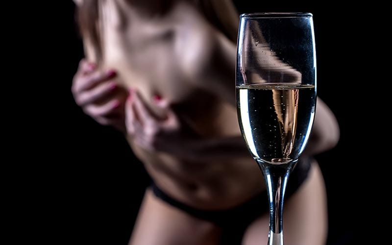 A glass of prosecco with a stripper in the background clutching her breasts