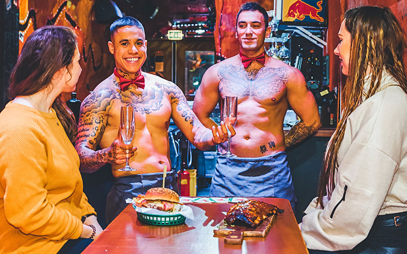Two topless butlers serving two women at a table