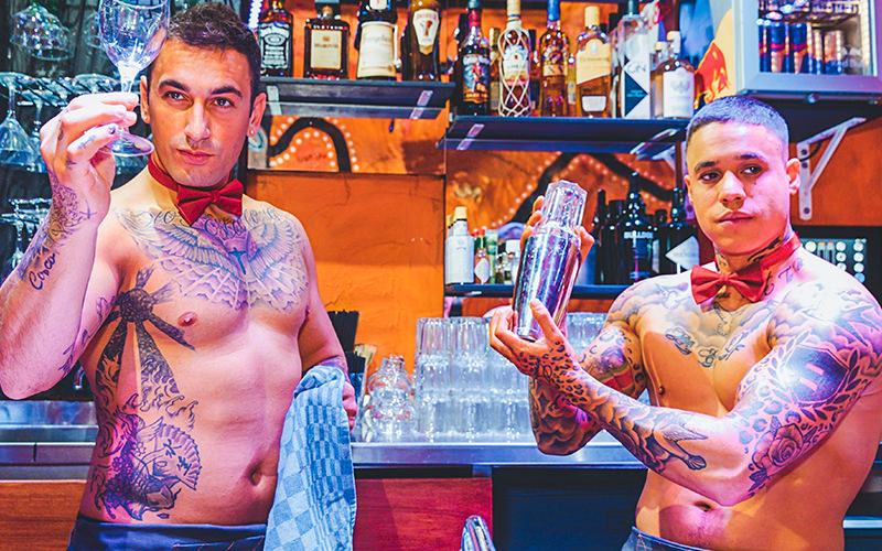 Two topless butlers making drinks behind a bar