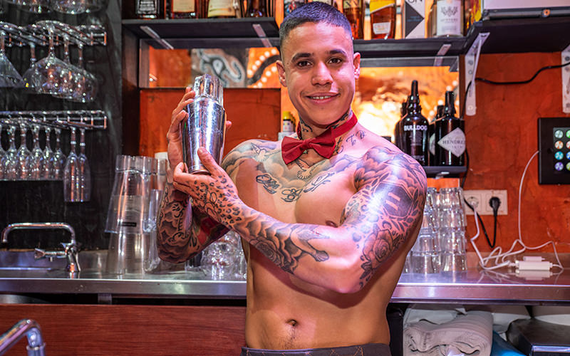 One topless butler making drinks behind a bar